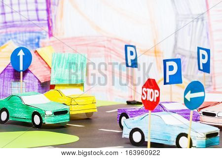 Road traffic in the toy town with handmade paper cars and signs model in driving school