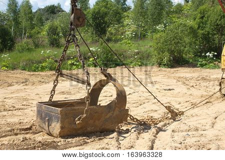 Big heavy bucket lies on sand on summer day before forest. Horizontal photo closeup