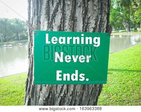 Text message Learning never ends on green board on tree