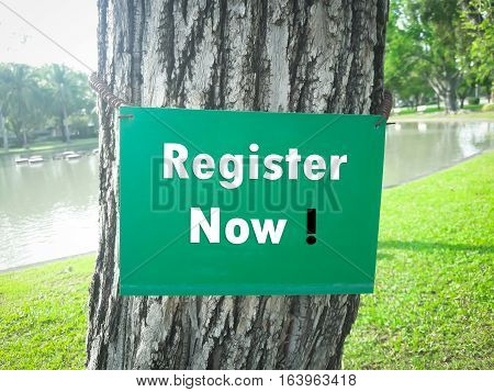 Text message Register Now on green board on tree