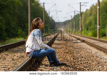 The girl sits on rails and thoughtfully looks in the sky.