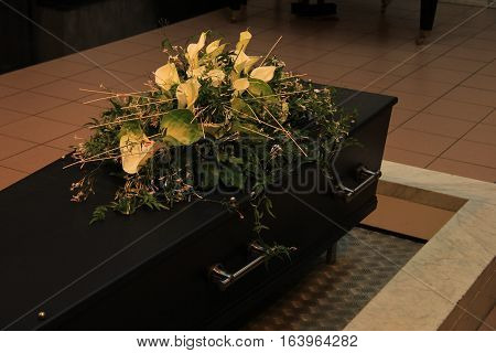 Wooden casket with funeral flowers cremation ceremony