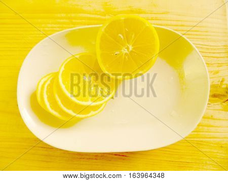on light wood chopping board is a white oblong dish with chopped fresh lemon rings with stones on a horizontal surface top view