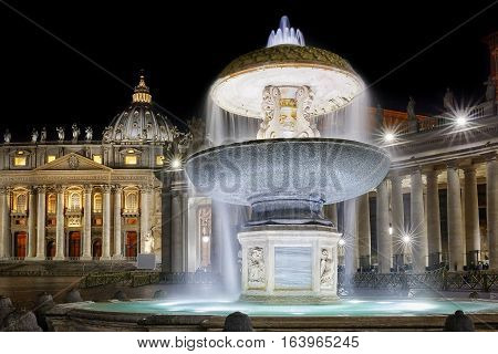 The so-called ancient fountain is one of two twin fountains placed in St. Peter's Square at the Vatican. Here at night shooting in a long exposure the background the facade and the colonnade of the temple basilica in Christendom.