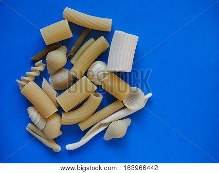 Many different types of Italian pasta including penne macaroni (maccheroni) fusilli spaghetti trenette (linguine) orecchiette tortiglioni conchiglie (shells) - blue background with copy space