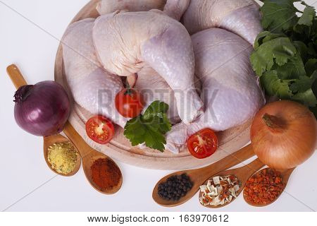 fresh chicken thighs and drumsticks on a wooden board with vegetables