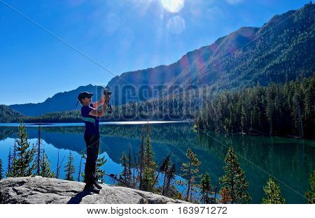 Woman on cliff above lake taking pictures. Snow Lake. Enchantment Lakes basin. Leavenworth. Seattle. Washington state. USA.