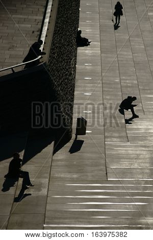 COLOGNE, GERMANY - NOVEMBER 24: The dark silhouettes of pedestrians and passersby on the banks of the Rhine at the Rhine promenade in the backlight on November 24, 2016 in Cologne.