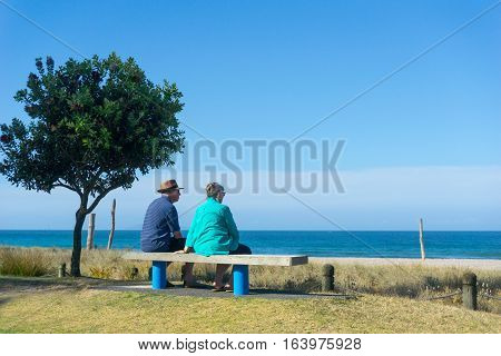 Mount Maunganui, December 21, 2016; Eldery couple rest and look at scenic ocean view on becnh seat along Mount Maunganui ocean-beach