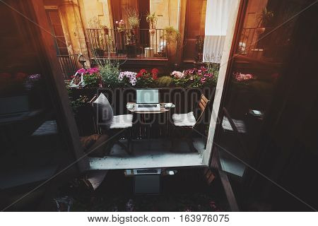 Small cozy beautiful workspace on balcony with laptop mouse smartphone chairs and flowers around on sunny summer day seeing through opened doors from dark interior facade of another house behind