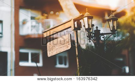 Close-up mock up of bright wooden planking signboard or banner with space for your text or logo hanging on a strings near street lantern on sunny summer day Barcelona Spain