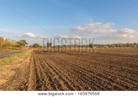 Newly ploughed field in the Essex countryside in late autumn on a bright sunny day. Shows a lovely blue sky with wispy clouds.