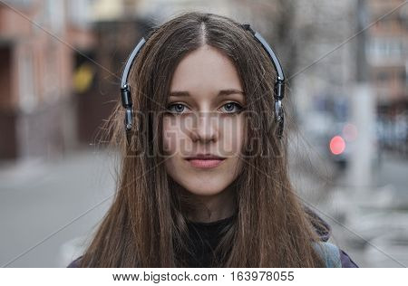 Girl hipster in headphones looking at camera, full face portrait