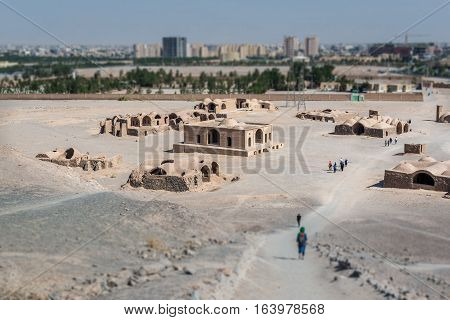 Tilt-shift effect photo of ritual buildings next to Zoroastrian Towers of Silence in Yazd Iran