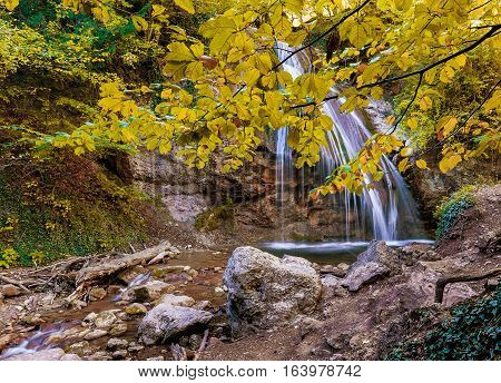 a waterfall Jur-Jur in Crimea with a branch of the tree in the foreground in beautiful autumn day