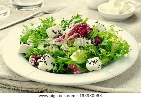 Green salad with spinach, frisee, arugula, radicchio, feta cheese and black sesame seed on blue wooden background, toned, horizontal
