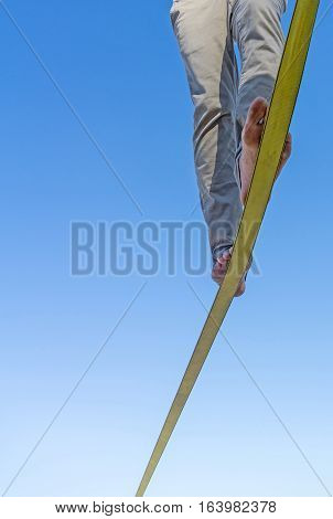 Two feet and legs on slack-line tape high in air against blue sky with balance and detrmination reaching the end slack-line