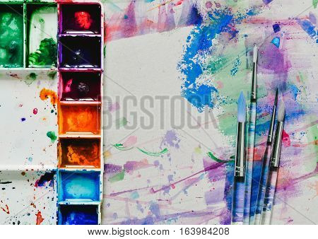 watercolor paints in palette with blobs of paint and a brush. Vintage stylized photo of paintbrushes closeup and artist palette