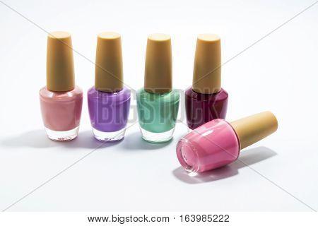 Many bottles of colorful fingernail paint for make up on white background.