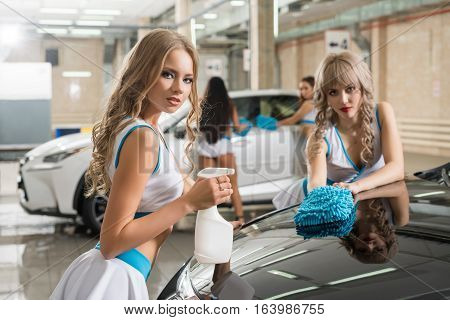 Sexy curly long haired blondes in fromula one style tops and mini skirts posing with pompons and sprayer near car at carwash