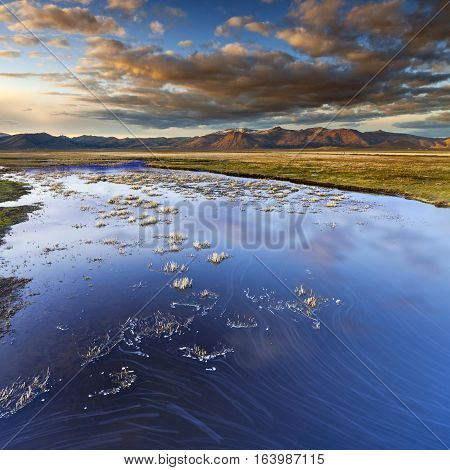 Wetlands In California At Sunset. River Leads Off Into The Distance Towards Mountain Range With Colo