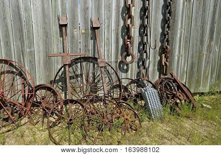 Old steel wheels and log chains lean against a wood fence in a salvage and junkyard