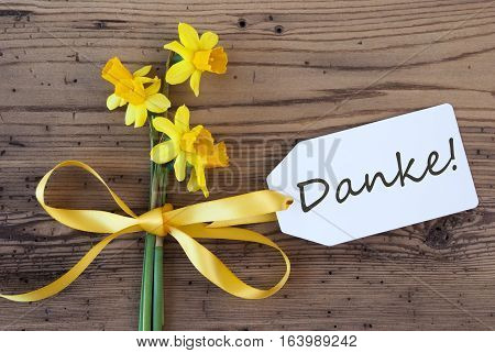 Label With Black German Text Danke Means Thank You. Yellow Spring Narcissus Or Daffodil With Ribbon. Aged, Rustic Wodden Background. Greeting Card For Spring Season