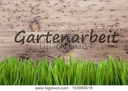 German Text Gartenarbeit Means Gardening. Spring Season Greeting Card. Bright Aged Wooden Background With Gras.