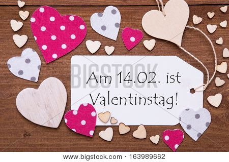 One Label With German Text Am 14.2. Ist Valentinstag Means February 14th Is Valentines Day. Flat Lay View With Wooden Vintage Background. Pink Wooden And Paper Hearts.