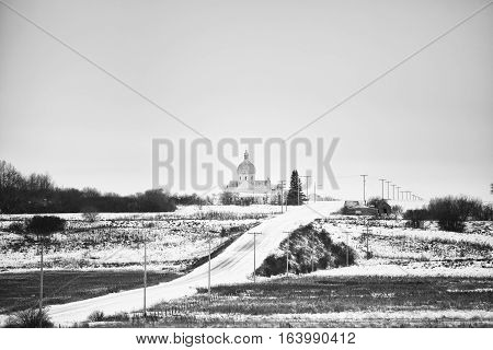 Steepled church beside a hilly dirt road in a winter black and white rural landscape