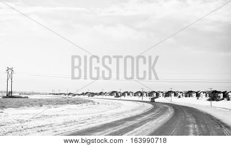 Row of cookie cutter houses along a two lane curving highway on the outskirts of a city in black and white winter landscape