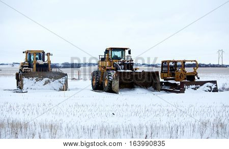 An industrial loader with bucket and two bulldozers prepared for snow removal parked on a snow covered field in winter landscape
