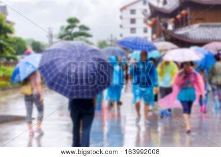 Blur Of People With Umbrella Walking In The Falling Rain