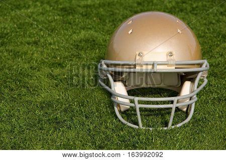 A gold American football helmet resting on turf