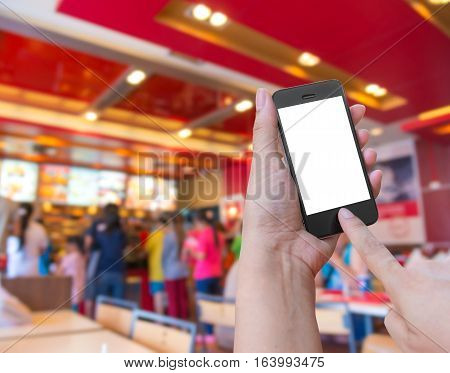 Hand holding and Touch on smartphone mobile with Order food online in restaurant background.