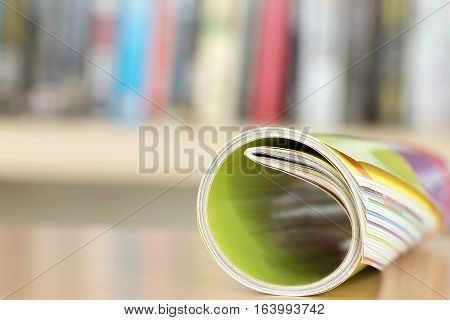 Close up edge of colorful magazine stacking roll with blurry bookshelf background for publication and publishing concept extremely DOF