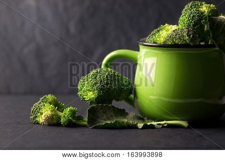 The still life with fresh green broccoli in ceramic cup on black stone plate