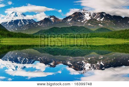 Landscape with mountain and blue sky reflected in water