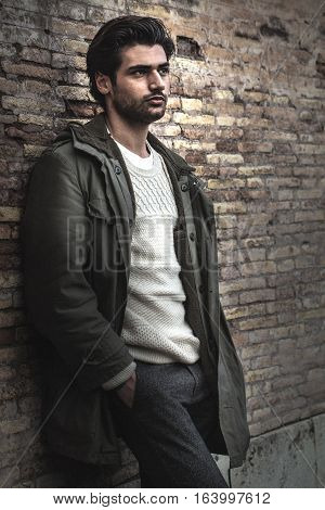 Young male urban city style on wall. A beautiful young man wearing winter clothes in the street. Pants, white sweater and green long coat. Hands in his pockets, leaning on an old wall. Intense attractive look, stylish hair.