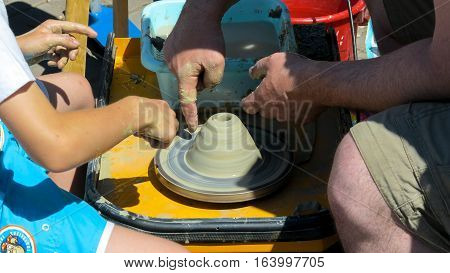 Male hand. Dirty hands in the clay and the Potter's wheel