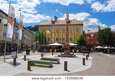 Lienz, Austria - July 16, 2014. View of Johannesplatz square in Lienz, with historical buildings, billboards, religious statue, commercial properties and people.