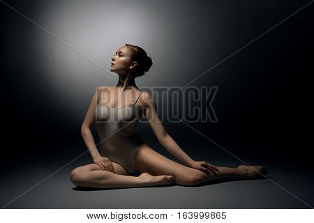 Female sexy gymnast in beige bodysuit posing on gray background sitting in split, looking up in profile studio shot
