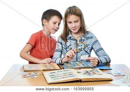 Teen Girl And Little Boy With Magnifier Looking His Stamp Collection Isolated