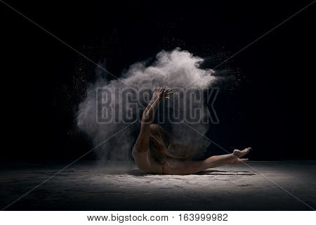 Female sexy gymnast with her blonde hair loose in beige bodysuit bending gracefully on black background with white dust all over body shot made in profile.