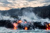 Molten lava flowing into Pacific Ocean from the Kilauea lava flow on Big Island of Hawaii under partly cloudy skies poster