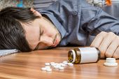 Young man commiting suicide. Overdose of medication. poster
