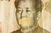 Mao portrait leader of China with closed mouth on a banknote of Chinese Yuan, as a symbol of the instability of the modern economy poster