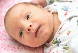 Cute Newborn Baby Lying In The Bed. Stock Photo