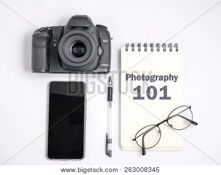 Photography 101 Lesson Concept, Top View Flat Layout Photographer Working Desk. DSLR Camera with smart phone notebook and eyeglasses poster