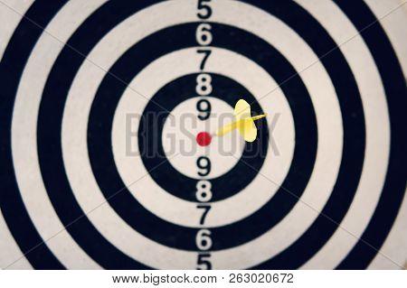 Dart Arrow Hitting The Target Of Dartboard On White Background. Hitting The Bulls Eye. Clear Aim. We
